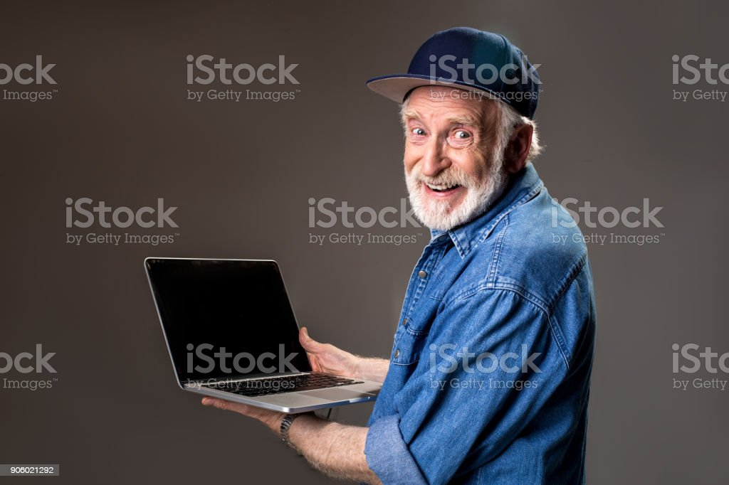 Glad hoary old man with computer stock photo