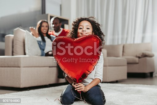 Family harmony. Calm girl looking happy while sitting in apartment with toy heart in hands. Parents on background. Focus on daughter