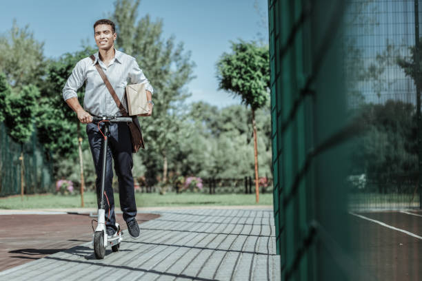glad male courier delivering package on scooter - electric push scooter stock photos and pictures
