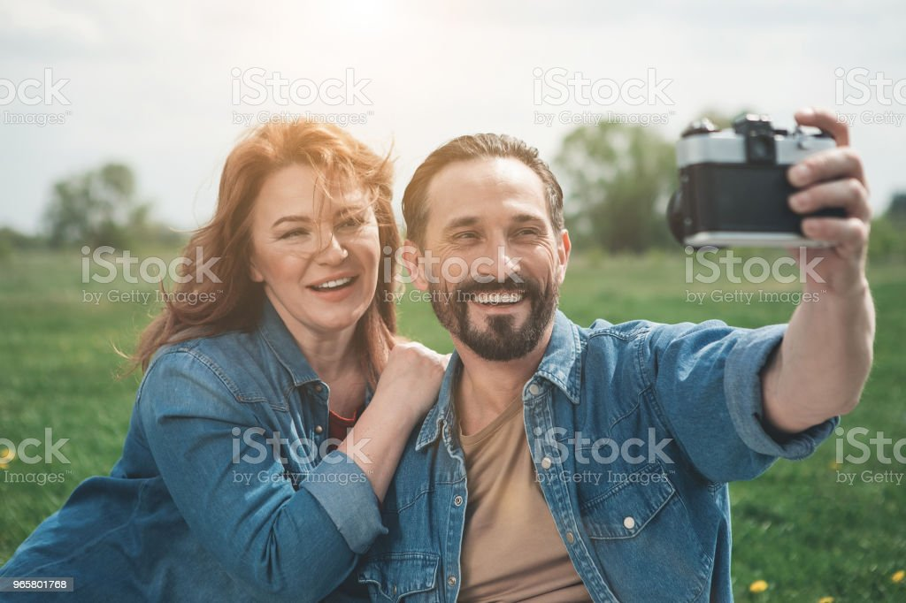 Glad married couple using camera in the nature - Royalty-free Adult Stock Photo