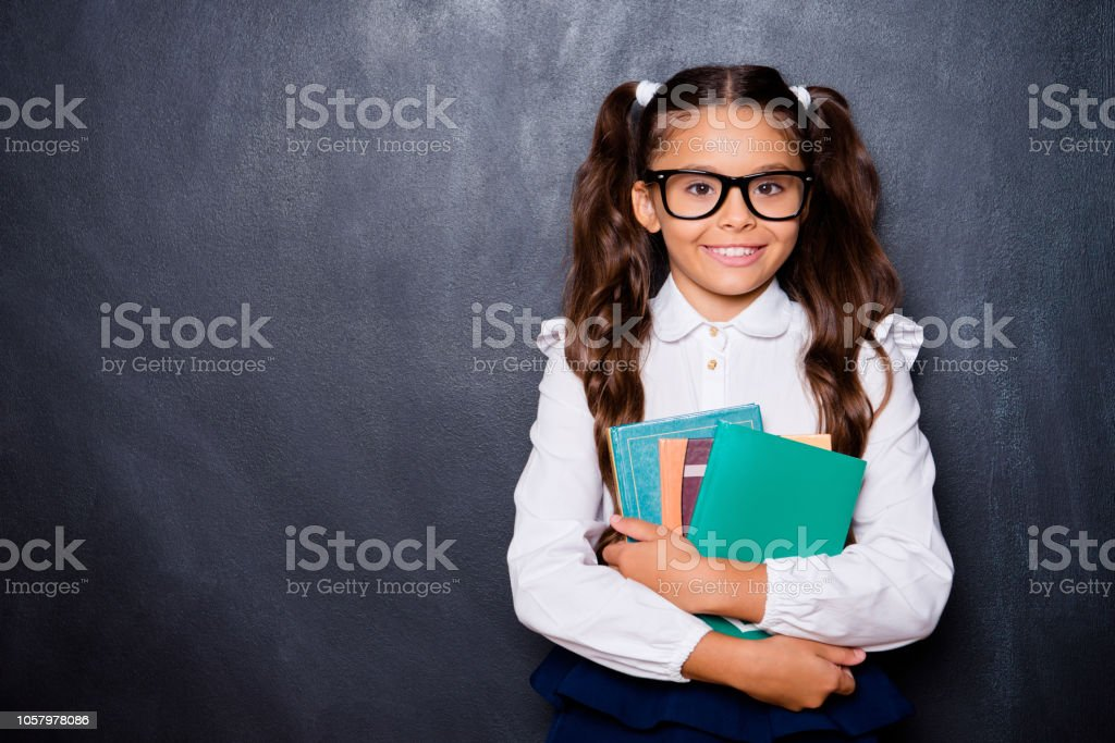 Glad positive nice smart cute small little girl with curly pigtails in white blouse shirt and blue skirt, carrying, keeping, hugging big book pile, copy-space. Isolated over black background stock photo