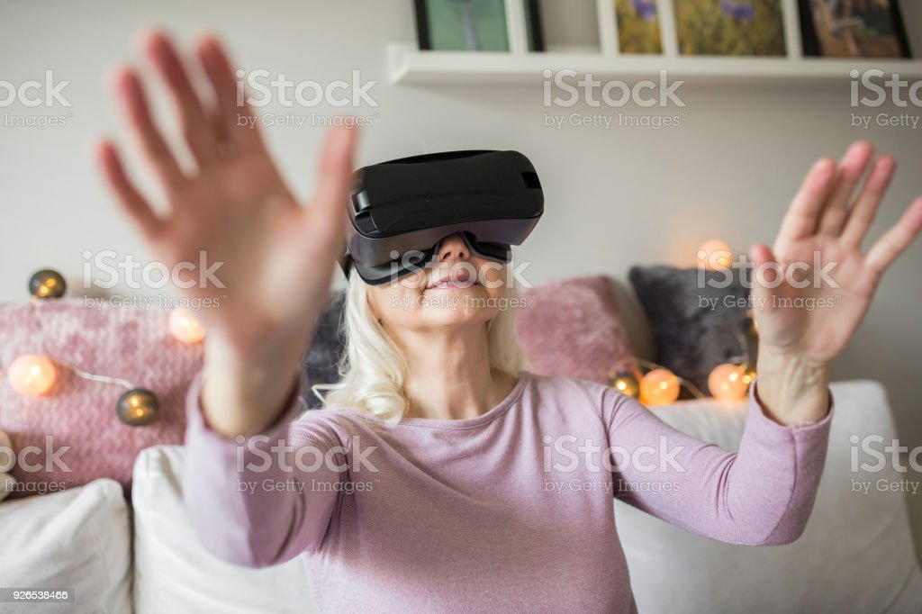 Glad senior lady having fun with vr headset stock photo