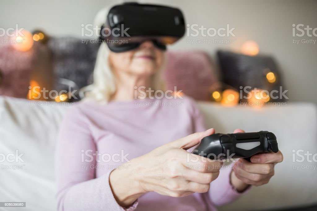 Glad senior lady using vr headset holding controller stock photo