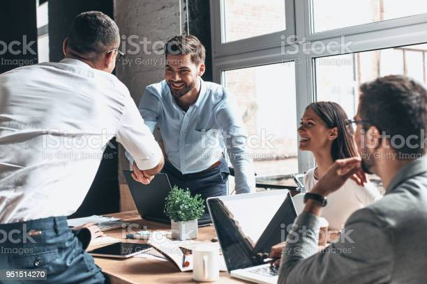 Young modern men in smart casual wear shaking hands and smiling while working in the creative office