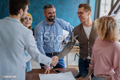 951514270 istock photo Glad to work with you! Young modern men in smart casual wear shaking hands and smiling while working in the creative office. 1158281400