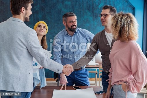 951514270 istock photo Glad to work with you! Young modern men in smart casual wear shaking hands and smiling while working in the creative office. 1158281402