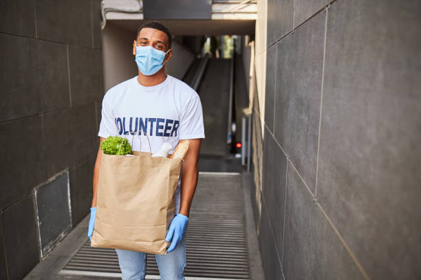 Glad volunteer in a face mask with a paper bag stock photo