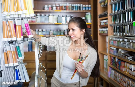594918592 istock photo Glad woman choosing various color in tube 594924114