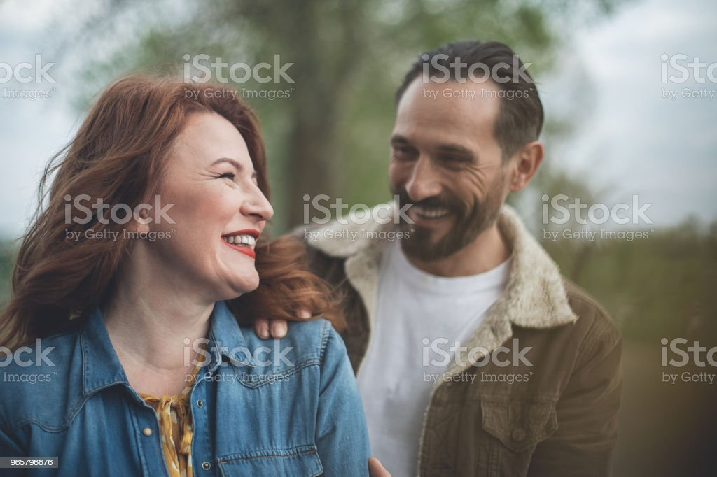 Glad woman enjoying hug of man in the nature - Стоковые фото Близость роялти-фри