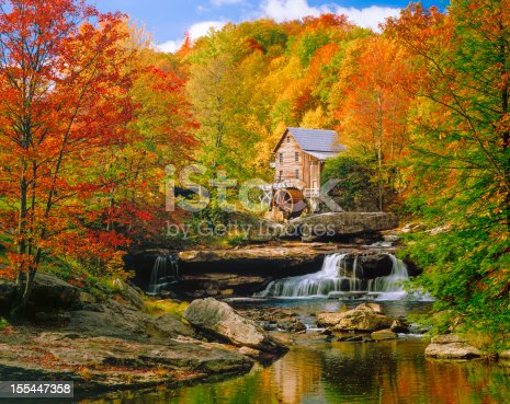 Picturesqe old Glade Creek Grist Mill with waterwheel and stream, in a blazing autumn colors setting.  Babcock State Park.