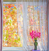 A bouquet of pink gladioli in a vintage ceramic vase on the windowsill against the background of a rural garden and yellow red leaves of maiden grapes in autumn sunny weather.