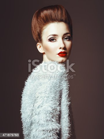 Studio portrait of beautiful glamourous woman with volume hairstyle, red lipstick and wearing fluffy jumper . Professional make-up and hairstyle. High-end retouch.