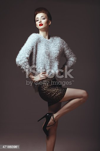 Studio portrait of beautiful glamourous woman with volume hairstyle, red lipstick and wearing fluffy jumper and mini skirt . Professional make-up and hairstyle. High-end retouch.