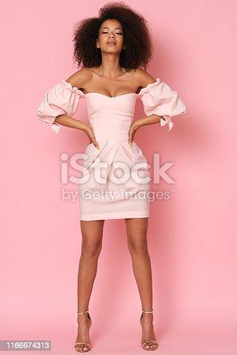 Studio shoot of beautiful model in pink dress.