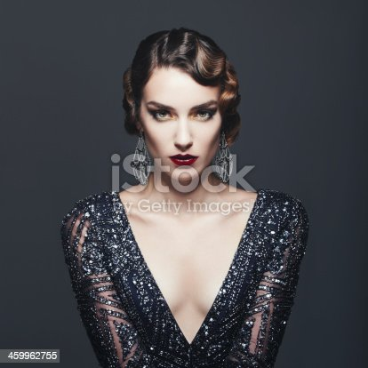 Studio portrait of beautiful glamourous  woman wearing shiny dress. 20's - 30's styled image. Professional make-up and hairstyle. High-end retouch.
