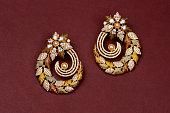 Glamorous antique Golden pair of earrings on red background. Luxury female jewelry, Indian traditional jewellery, kundan earring,Bridal Gold earrings wedding jewellery,Vintage earring