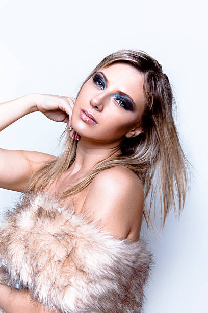 Glamorous beautiful blond woman with faux fur stock photo