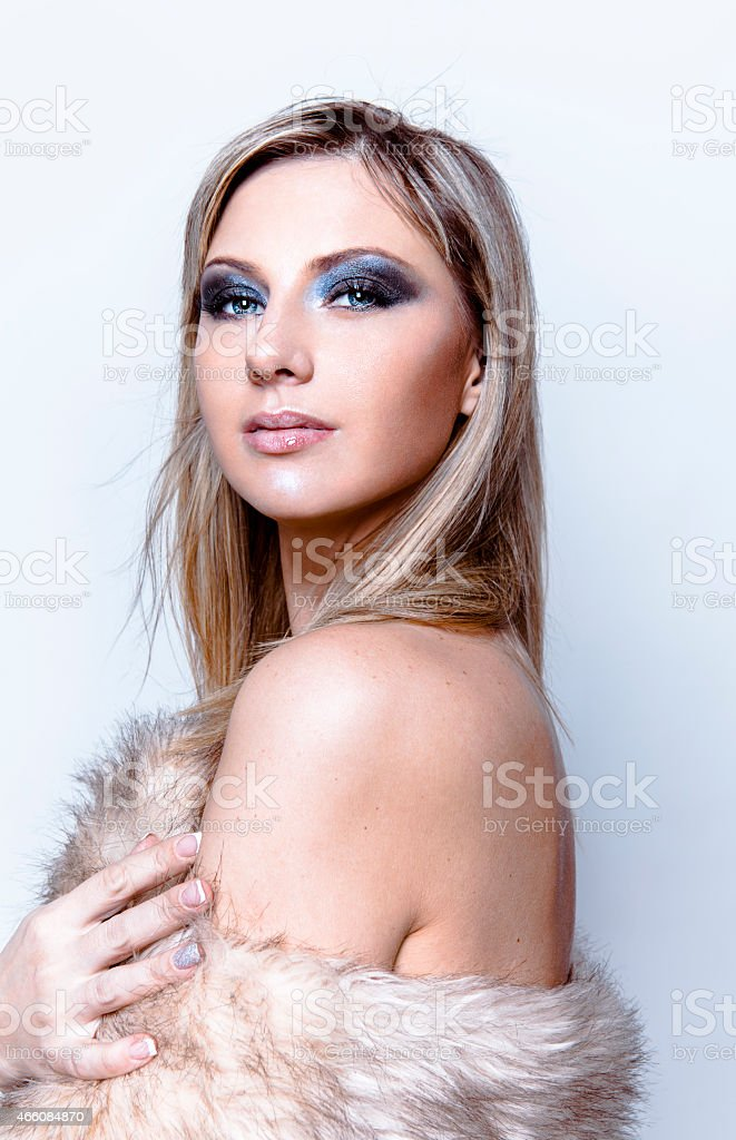 Glamorous beautiful blond woman with faux fur stock photo