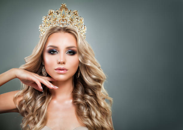 Glamorous Blonde Woman with Golden Crown, Makeup and Wavy Hair. Cute Fashion Model with Diamonds Jewelry, Shiny Curly Hairstyle and Make up Glamorous Blonde Woman with Golden Crown, Makeup and Wavy Hair. Cute Fashion Model with Diamonds Jewelry, Shiny Curly Hairstyle and Make up tooth crown stock pictures, royalty-free photos & images