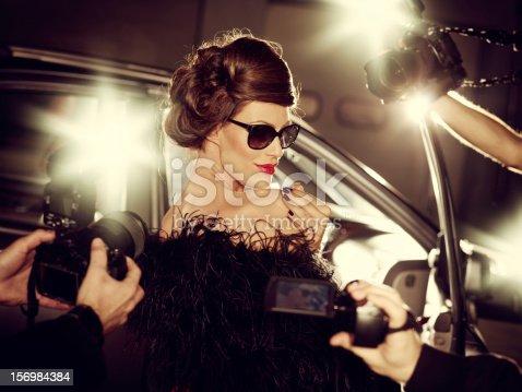 istock Glamorous Celebrity Woman Surrounded By Paparazzi Photographers 156984384