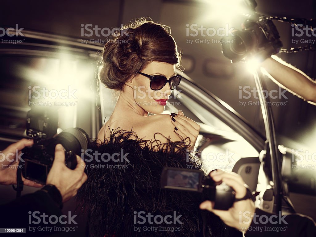 Glamorous Celebrity Woman Surrounded By Paparazzi Photographers stock photo