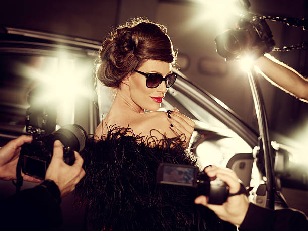 glamorous celebrity woman surrounded by paparazzi photographers - celebrities stock pictures, royalty-free photos & images