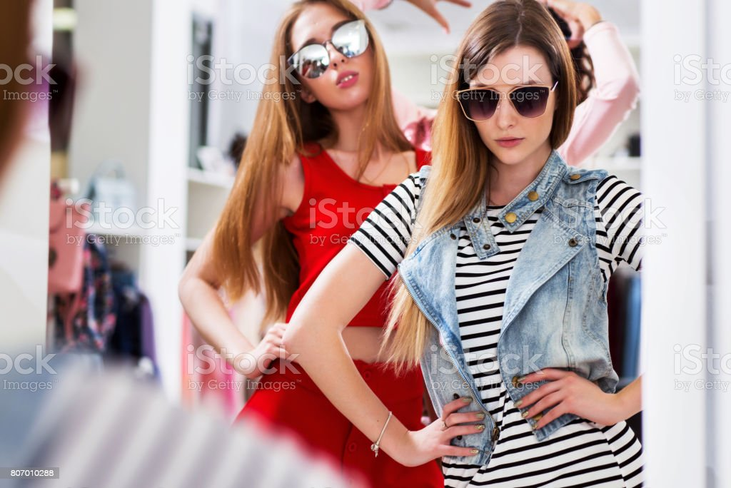 Glamorous girls trying on sunglasses posing in front of the mirror in fashion boutique stock photo