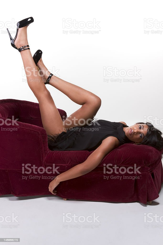 Glamorous model Afro American woman on red couch royalty-free stock photo