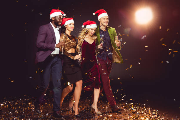 6ebcd3cce33e1 glamorous multiethnic friends in santa hats holding champagne glasses and  walking on confetti with backlit stock