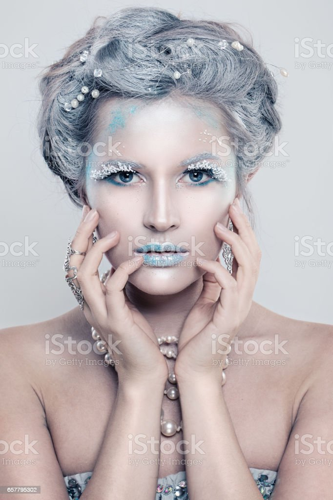 Glamorous Winter Fashion Model Woman with Glitters Makeup. Beautiful Girl with Snow Hair Style and Accessories stock photo
