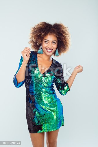 Stylish young afro american woman wearing shiny green colored dress and dancing against white background