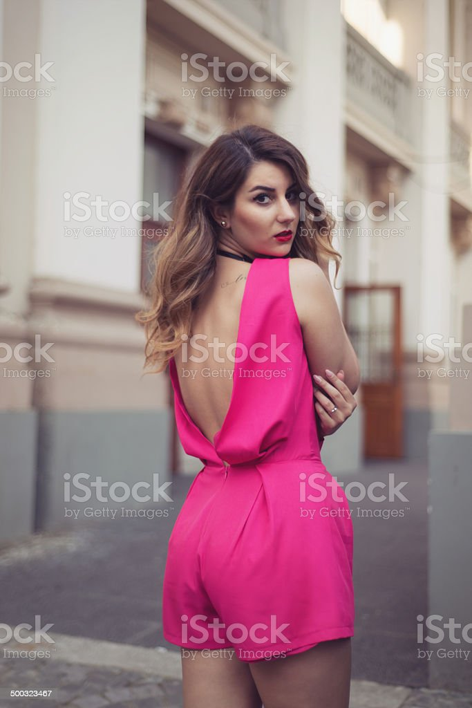 Glamorous woman dressed in a sexy sleeveless pink jumpsuit stock photo
