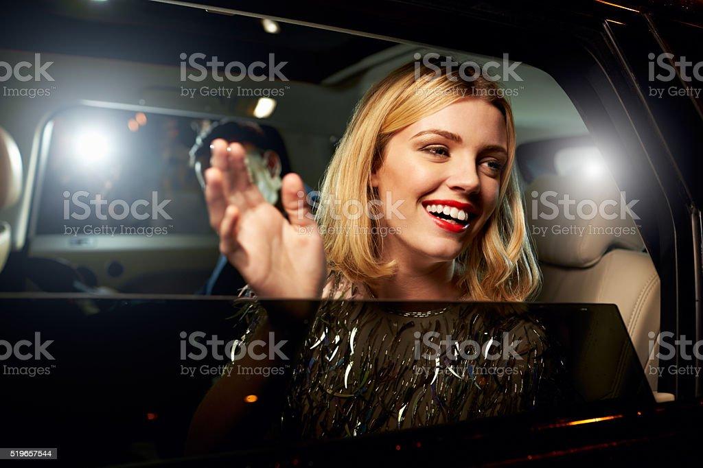 Glamorous woman waving through the window of a limousine stock photo
