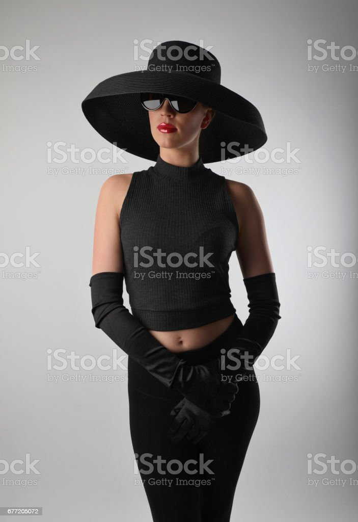 Glamorous woman wearing vintage fashion including black hat with evening gloves stock photo