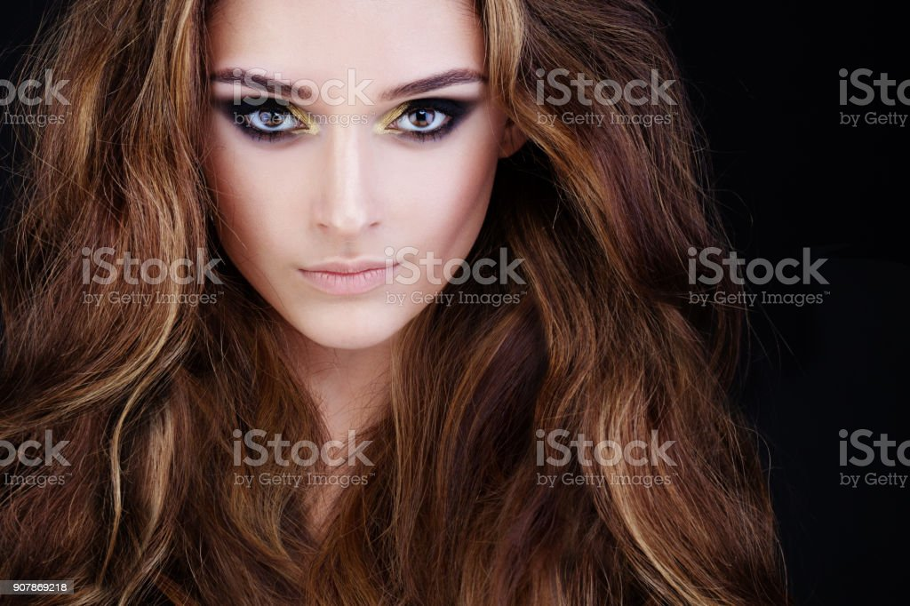 Glamorous Woman with Long Permed Hair and Smokey Eyes Makeup stock photo
