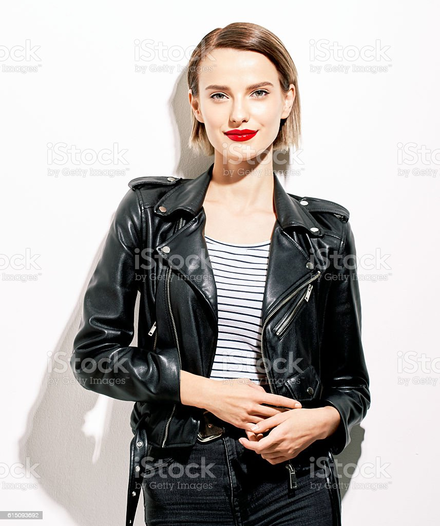 Glamorous young woman in black leather jacket on white background stock photo