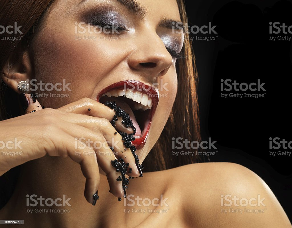 Glamorous Young Woman Licking Caviar Off Fingers royalty-free stock photo