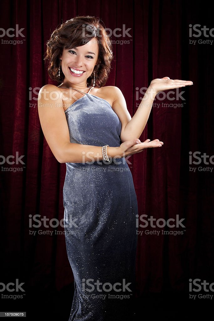 Glamorous Young Woman Presenting in Front of Red Curtain stock photo