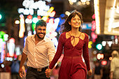 Latin American woman and mixed race man, in their 20's, wearing party clothes, having fun together with woman walking ahead smiling and bright city lights in background