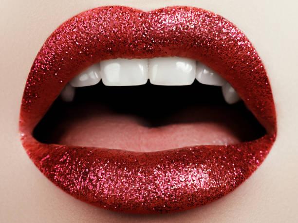 glamour fashion knallrote lippen make-up mit glitzer. makroaufnahme einer frau gesicht teil. sexy glänzenden lippen make-up, luxus lady - vampir schminken frau stock-fotos und bilder