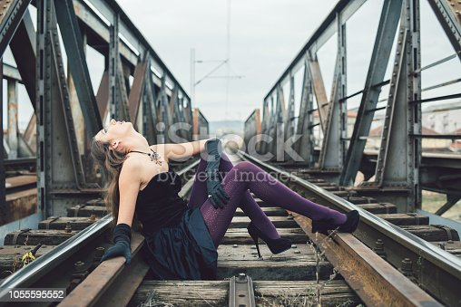 Young glamorous goth girl in a black and purple outfit posing on a metal train bridge