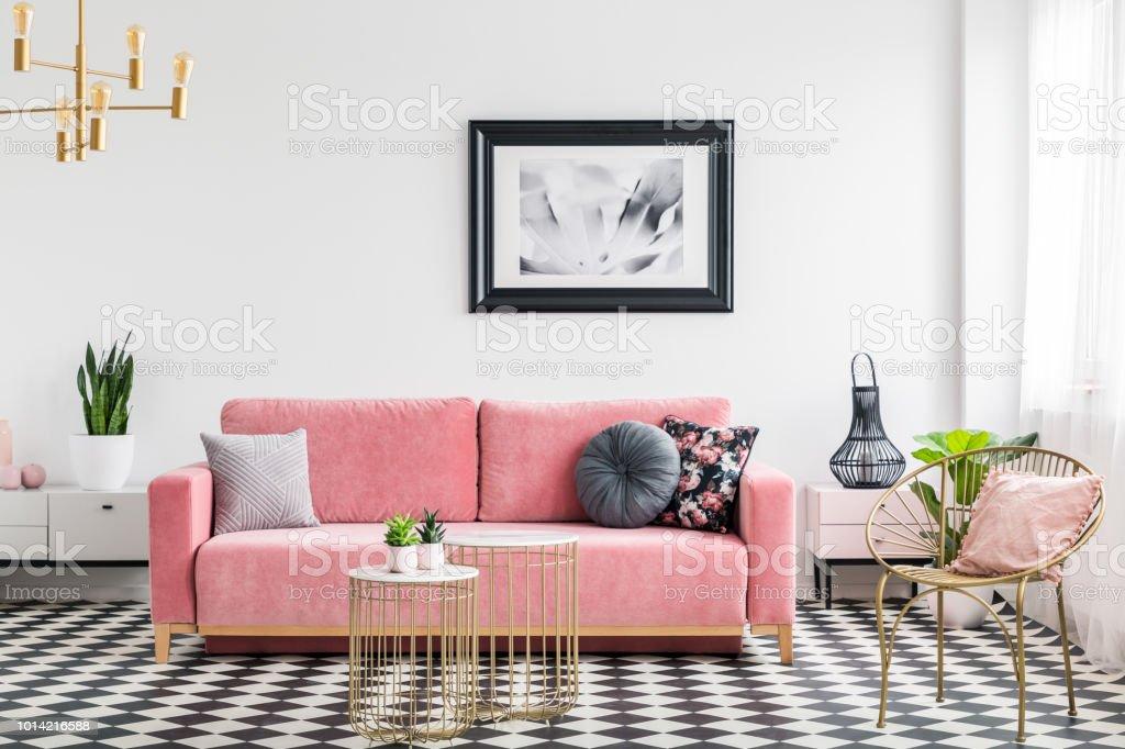 La vie glamour room intérieure avec un canapé rose, fauteuil doré et tableaux, peinture et damier carreaux. Vraie photo photo libre de droits