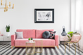 Glamour living room interior with a pink sofa, golden armchair and tables, painting and checkered tiles. Real photo