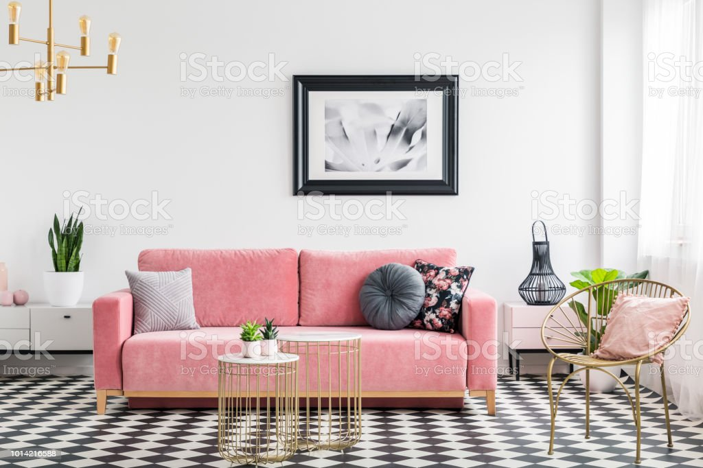 Glamour living room interior with a pink sofa, golden armchair and tables, painting and checkered tiles. Real photo stock photo