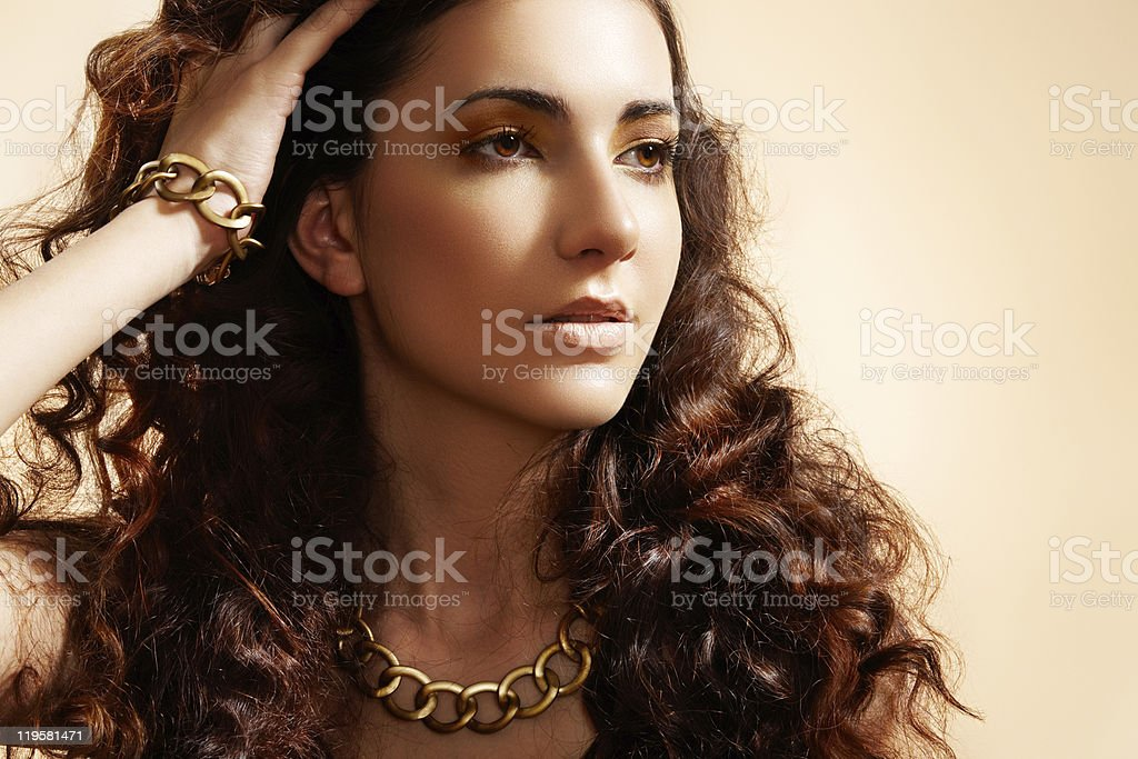 Glamour model with shiny gold jewelry, volume hair stock photo