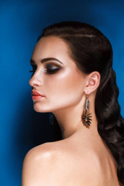 glamour portrait schöne brünette frau modell mit abend-make up und hollywood frisur auf blauem hintergrund - blaues augen make up stock-fotos und bilder
