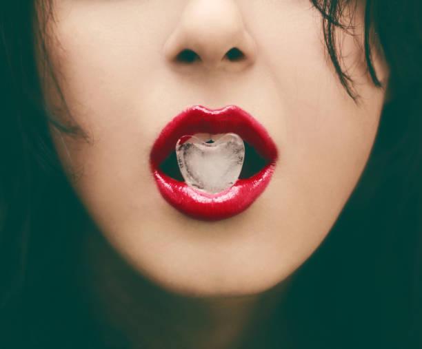 glamour portret - rode lip houden hart vorm ijs - verleiding stockfoto's en -beelden