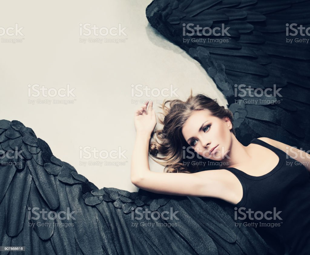 Glamour Woman Fashion Model Black Angel Relaxing stock photo