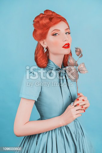 Glamour woman in blue retro dress. Minimal color concept. Redhead model with retro hairstyle on pastel blue background. Pastel color. Lady elegance. Magnificent wear. Minimal style in glamour