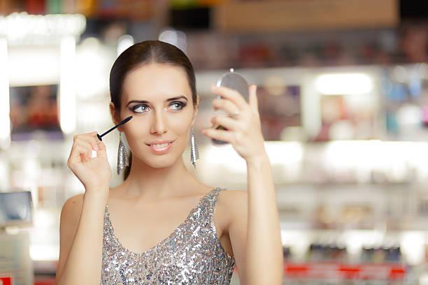 glamour frau, die mit wimperntusche und make-up-spiegel - anzieh nacht stock-fotos und bilder